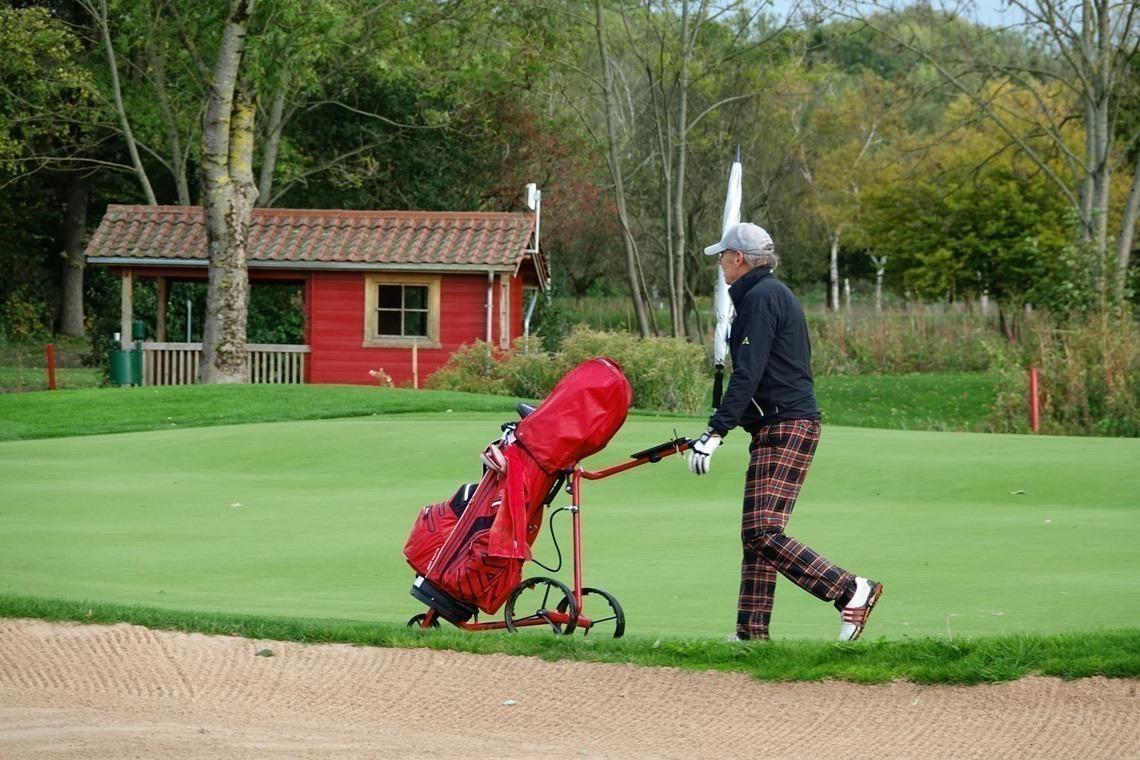 Immer stilecht: Karo-Hose und rotes Bag vor roter Hütte
