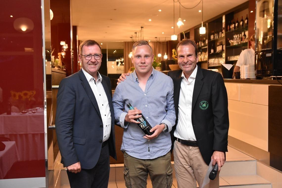 """268 Meter weit schlug Moritz Markert seinen """"Longest Drive"""". Präsident Karl-Friedrich Löschhorn, links, und GF Wolfgang Michel überreichten den Bio-Wein von Costa Navarino als Preis."""