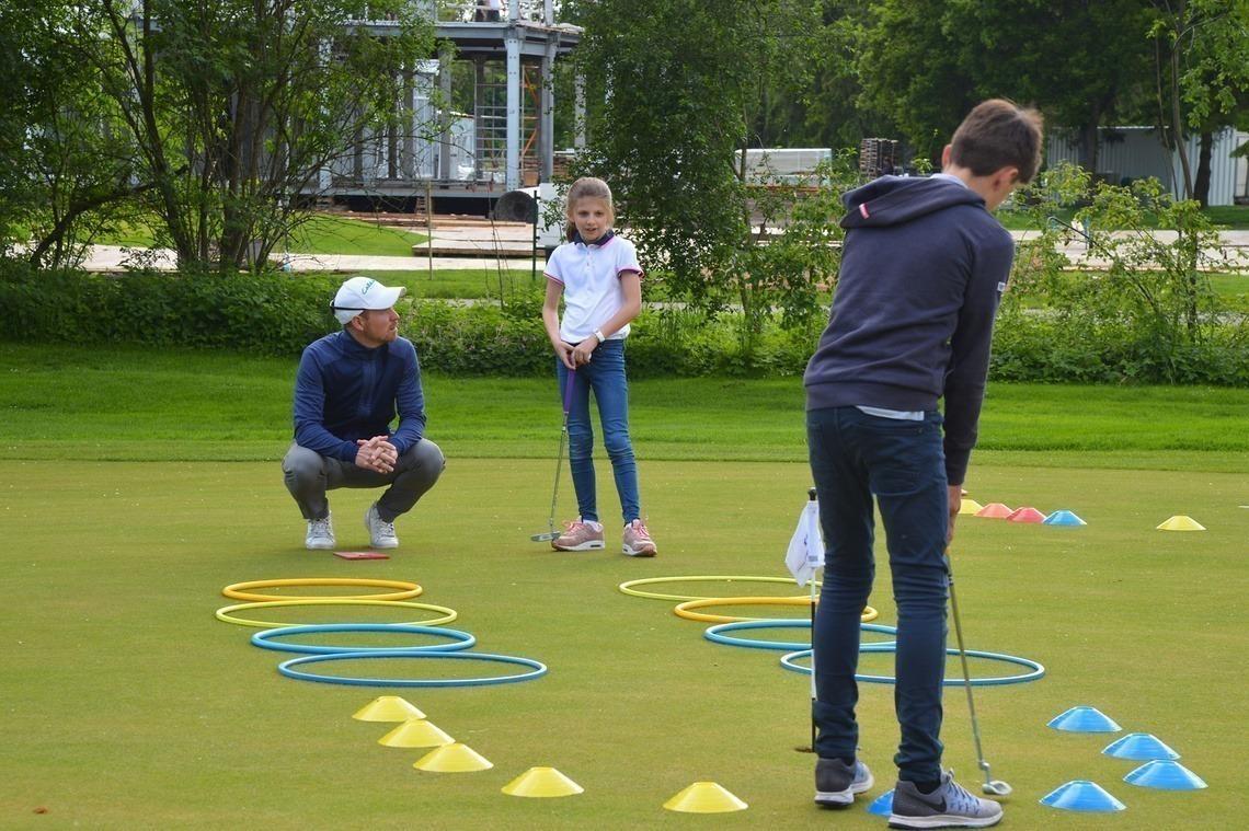 Mini-Golf für den Nachwuchs mit Pro Fabian Michelberger (in der Hocke)
