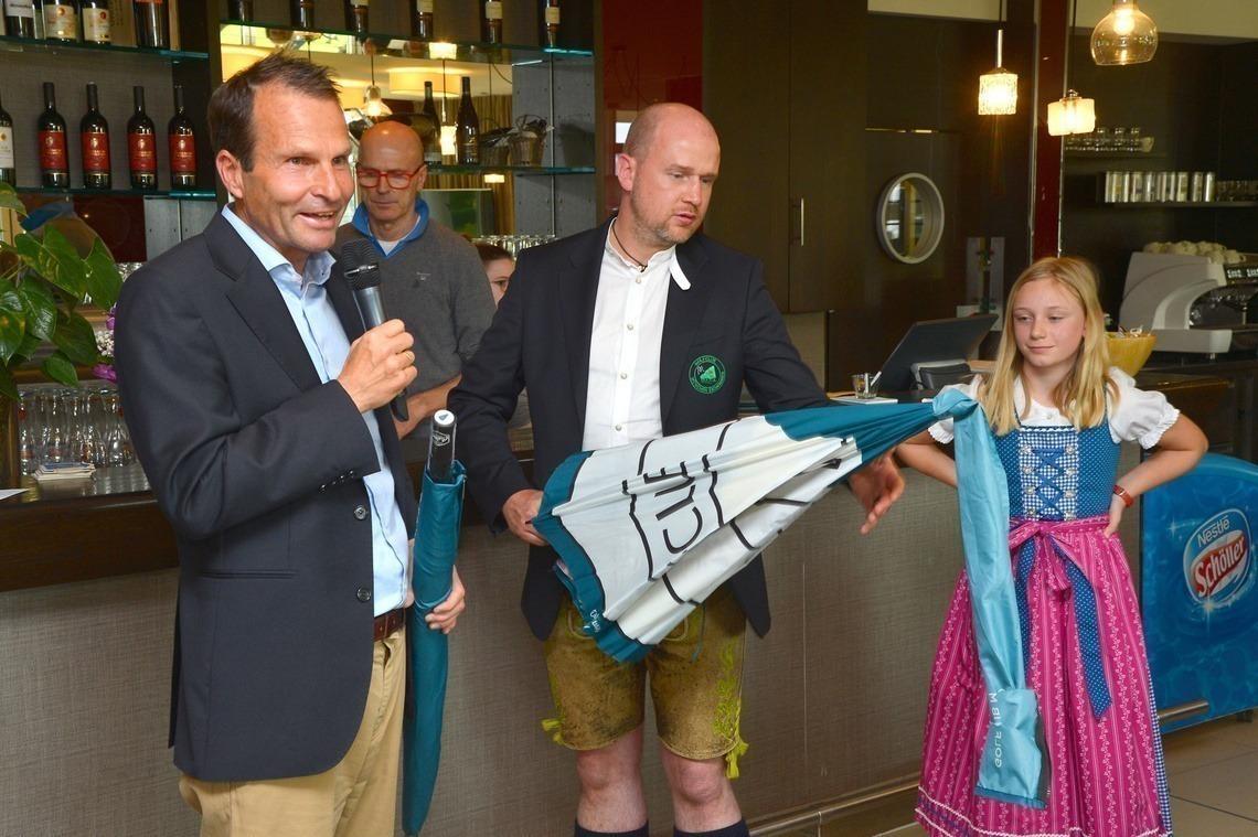 Geschäftsführer Wolfgang Michel bedankte sich bei Sponsor Kai Pierre Thieß für sein Engagement; daneben Chiara Aumann, versteckt dahinter Wirt Uli Sauer