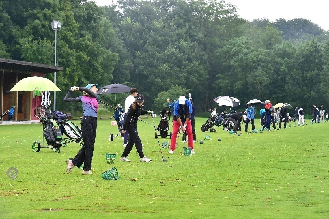 Vor dem Turnierstart wurde auf der Driving Range eifrig trainiert – noch mit Regenschirm und Regenanzug.